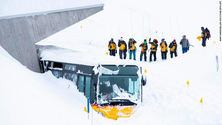 epaselect epa07275740 A bus caught by an avalanche next to Hotel Saentis, with search-and-rescue workers, on the Schwaegalp, Switzerland, in Hundwil, Switzerland, 11 January 2019. According to local police, an avalanche has hit the the hotel 'Saentis' on 10 January afternoon, burrying cars and part of the restaurant. Several people were injured, the report stated.  EPA-EFE/GIAN EHRENZELLER